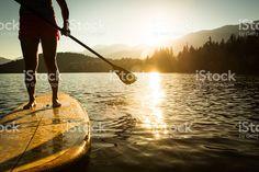 Paddleboarding on lake during sunrise or sunset. royalty-free stock photo