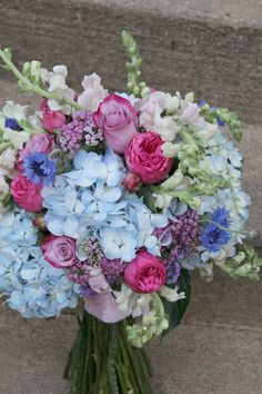 Bridal bouquet made up fresh blue hydrangeas, light pink snap dragons, blue cornflowers, pink piano peony roses, pink yarrow and pinky purple roses.