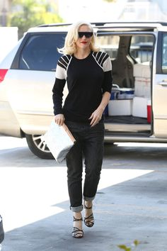 Gwen Stefani in baggy boyfriend jeans, black and white sweater, graphic sandals and a white clutch