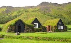 Green Roof Design - This green roof design is built on smaller houses, instead of a university like the first one. In this case the grass is growing from the ground sloping up onto the roof giving the house a curved effect.