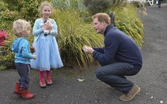 Prince Harry receives some flowers from Mia (six) and Liam (three) Squires during a visit to Stewart Island