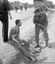 A British soldier talks to an emaciated prisoner. The prisoner, Louis Bonerguer, was also British and had been dropped by parachute to work in German occupied territory in 1941. After his capture, he was interned at Belsen. / UK Imperial War Museum