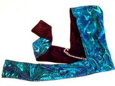 Blue/teal peacock slinky shiny spandex/ black velvet reversible scoodie. Grommets with silver colored chains.