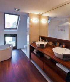 Łazienka na poddaszu urządzona jest przytulnie i ze smakiem. Drewno w projekcie łazienki ociepliło surowe wnętrze, a wygodne rozmieszczenie stref stworzyło funkcjonalne, rodzinne wnętrze.