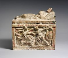 Ash urn for Arntile, freedman of the Afuna family -- Etruscan terracotta cinerary urn, 2nd c. B.C., Hellenistic.  Frieze showing a warrior using a plow as weapon.  Metropolitan Museum of Art, New York