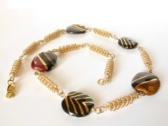 Kazuri beads in bronze, gold and black alternate with delicate 14K gold filled wire hand-coiled beads in this handmade necklace by DianaShyeJewelry on Etsy.  The lovely ceramic Kazuri beads are made by women in Kenya, Africa. They are marketed by a company that belongs to the Fair Trade Federation and their sale helps the women artists and their families raise their standard of living above the poverty line.  $169