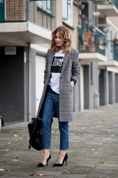 Fashion Me Now looking chic in a long checkered coat, graphic tee, and jeans