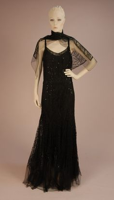 1930s Sleeveless black net evening dress with low back and narrow strap, having floral applique lace decorated allover with flower shaped black sequins, fitted through the hip, with full gored skirt forming a band of large Van Dyke points, plain net hem band, attached silk under dress. Matching scarf with flared ends. Via Whitaker Auctions.