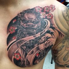 black and grey Chinese foo dog/ fu dog chest plate tattoo with colored cherry blossom flowers by Khang Vo of Anvil Tattoo Co.
