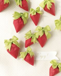 Strawberry-shaped tissue paper packets with leafy bows are stuffed with caramelized almonds dipped in dark chocolate