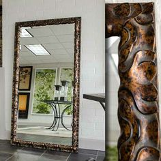 A large floor mirror with an espresso-colored frame. The frame is ...