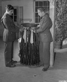 US Army Privates Kotula and Queen hanging stockings on Springfield M1903 rifles for the Christmas season, Camp Lee, Virginia, United States, Dec 1941