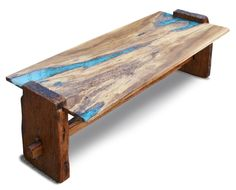 This coffee table started with a beautiful cross section of a white oak stump. A river of epoxy resin and turquoise chips fills the varied irregularities of the wood. Thick rustic end pieces provide t