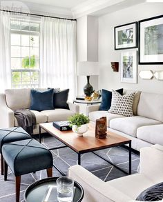 A fresh and modern living room in a Toornto Beaches house. The color is kept neutral (off white, with blue accents). The blue accents is throughout the home and ties the whole space together. The wood coffee table top adds warmthy while its open frame balances out the bulkiness of the sofa and loveseat. Love the dark blue stools and cozy dark blue rug. #homedecorlivingroomcozy