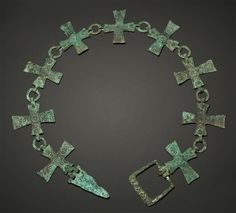 Byzantine bronze collar or belts formed by nine crosses with decoration of concentric circles, the buckle engraved with four Greek letters: ' TOMY '.  5th-6th Century AD