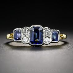 Newly crafted in London, England, this refined, low-profile ring features three rich royal-blue emerald-cut sapphires alternating with pairs of bright white mine-cut diamonds presented in timeless late Edwardian/early-Art Deco style. Crafted in crisp platinum and rich 18 karat gold, with a scalloped open gallery and delicate milgrain engraving. A low-profile beauty. In a finger size 7, stamped with abundant English hallmarks. Three emerald-cut sapphires total 1.22 carats.