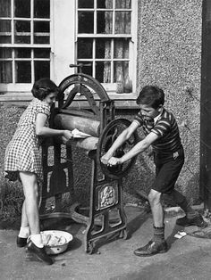 Children putting washing through the mangle to wring it dry for their mother, 1941