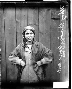 Mary Bimbo, Romani girl, standing in front of a wooden fence with her hands on her hips  Half-length portrait of Mary Bimbo (Mrs. George Bimbo). This image was probably taken in Chicago, Illinois.  1913