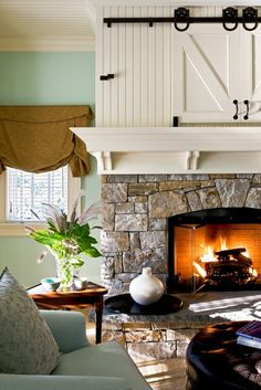 Barn doors above the fireplace hide a TV.