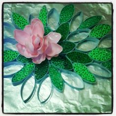 Create a water lily wall art. Recycled paper towel rolls, old pony beads and melted plastic spoons.
