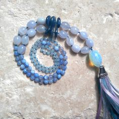 Handmade unique mala necklace.  Opalite, Blue Jade, Chalcedony and Blue Agate with handmade ribbon tassel.  108 beads.  Hand knotted between each bead and gemstone to keep the necklace secure and strong.