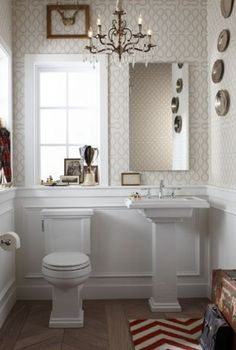Adorable powder room design with wainscoting, white pedestal sink, wood floors in a herringbone pattern, red & white zigzag chevron rug, beige wallpaper and bronze crystal chandelier.