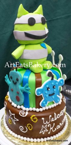 Lil Monster's neon green, brown and blue fondant creative baby shower cake design with edible monster topper
