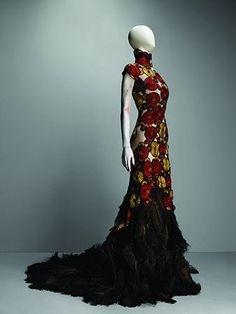 * Alexander McQueen (British, 1969–2010)? Dress VOSS, spring/summer 2001. Nude synthetic net appliquéd with roundels in the shape of chrysanthemums embroidered with red, gold, and black silk thread with black ostrich feathers. Photo Sølve Sundsbø