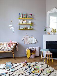 On adore le berceau en rotin qui s'accorde magnifiquement avec le tapis berbère et le miroir à moulures de la cheminée, un mélange des styles réussi !