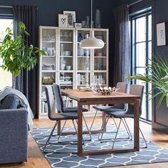 En brun og grå spiseplass med fire komfortable, polstrede VOLFGANG forkrommede stoler i grått, og MÖRBYLÅNGA bord i eikefiner.