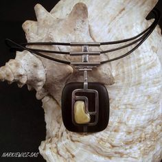 Silver 925, handmade, elegant necklace.   Charming small natural amber  is  on the ebony  square size 3.5cm.  Decorative element  size: 6cm x 3.5cm. Pendant hangs on   3 black leather thongs. Necklace length: 45.5cm plus 3cm   extra chain.  ALWAYS FREE SHIPPING FOR ALL CUSTOMERS IN U.K.