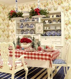 Christmas Kitchen-Simple and pretty kitchen decor gets a Christmas makeover with some well-placed jingle bells, tiny trees, and a cross-stitched Christmas scene hanging on the cabinets. Draw attention upward with a surprising wreath of evergreen around chandeliers.