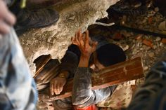 Nepalese rescue personnel help a trapped earthquake survivor, as his friend lies dead next to him in Swyambhu, in Kathmandu on April 26, 2015.