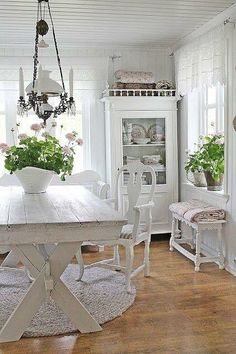 Gorgeous white farmhouse dining room.  I love the old lamp above the table. #farmhouse #shabbychic #diningroom #white