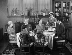 A family gathers round the table in the 1940s as they are served roast turkey by their maid.