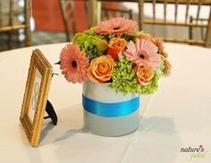 Colorful reception centerpiece with pink gerbera daisy, roses, green hydrangea and billy ball accents.