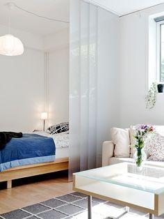 suelo de tarima suelo de gress negro sofa blanco separación de salón y cama separación de ambientes mini pisos mampara en el salón lámpara de diseño diseño de interires decoración espacios pequeños decoración de interiores decoración de estudios pequeños cocinas blancas