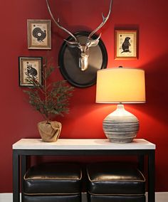 The lower level family room/theater room has a vignette of framed vintage hunting target advertisements around a mounted silver deer head. The home is on Deer Lake in Clarkston.