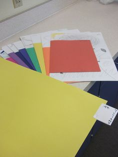 Inside each portfolio is a color coded folder (made of construction paper) for each of my art room tables.  I have hanging shapes over each table in colors red, orange, yellow, green, blue, indigo, violet and red violet.