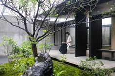 Benches are suspended from the roof of this compact glass-walled tea house, which faces out onto a landscaped garden squeezed onto a small plot in Shanghai.