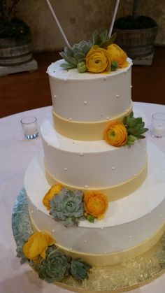 Wedding Cake flowers including green succulents and brilliant gold ranunculus