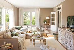 Salón en tonos crema y beige con sofá con chaise longue, aparador de madera, doble mesa de centro y cortinas