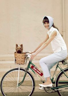 Audrey Hepburn and her dog Assam of Assam photographed riding around the Warner Brothers Burbank Studio during the production of My Fair Lady, 1963.