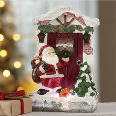 "Beautiful hand-carved and hand-painted Santa in lit front-door scene. Resin. Uses 3 AAA batteries (not included). 6 3/4"" w x 10 1/4"" h x 3 1/4"" d."