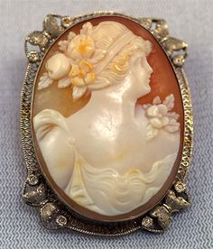 circa 1920, classically carved shell cameo, set in an uncommon mounting! Intricate 14K white gold filigree features a pretty engraved butterfly at each corner of the frame