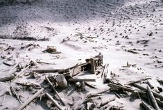 A wrecked logging truck and crawler tractor are shown amidst ash and downed trees near Mount St. Helens on May 20, 1980, two days after an explosive eruption.