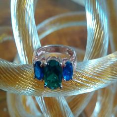 Emerald and sapphire rose gold ring. Oval prong set  3 stone simulated emerald and sapphires on rose gold over sterling silver ring. Beautiful scrolling details, tw 3.66 carats. Size 5. Jewelry Rings