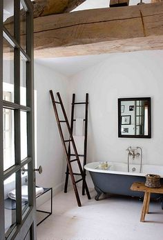 rustic yet modern bathroom with  black claw foot tub and great ladders as towel racks and glass paned door