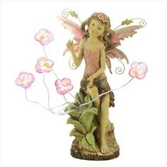"""Peony Fairy Solar Statue by Statue. $75.00. Polyresin. Two AA 300MAH NI-CD batteries included. 12"""" x 11"""" x 18"""" high.. A sweet young fairy pauses to admire a new-found patch of blushing blooms, blessing your garden with the beauty of spring. Enjoy this statue both day and night, thanks to tiny solar lights nestled inside each lovely flower!"""