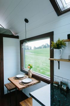 A 24' luxury tiny house on wheels with a butcher block table and benches in front of a large window, providing a wonderful view of wherever you are on your journey.
